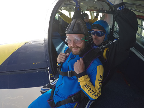Gaz sat on the edge of a plane about to Skydive